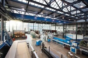 """<div class=""""bildtext"""">Das Technologiezentrum von Jansen: Aluminiumwerkstatt, Stahlwerkstatt, Maschinenpark und Prüfzentrum (rechts) in einer Halle, auf einer Ebene.</div>"""