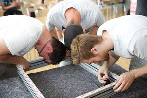"""<div class=""""bildtext"""">Die Schüler helfen beim Zusammenbau des Fensters mit: Drei angehende Metallbauer setzen die Eckelemente der Mitteldichtung in den Rahmen.</div>"""