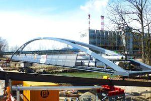 """<div class=""""bildtext"""">Die Stabbogenbrücke wurde in lediglich acht Stunden mit Litzenhebern in ihre Endlage """"abgeseilt"""".</div>"""