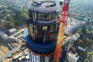 """<div class=""""bildtext"""">Schwindelfreie Monteure haben die Fassadenelemente am sogenannten Bierfass auf ca. 140 Meter Höhe installiert.</div>"""