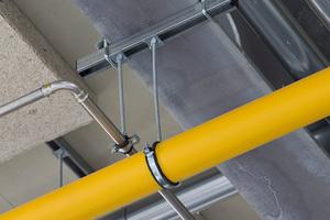 Ein Beispiel für die Befestigung einzelner Rohrleitungen an Trägerprofilen mit kurzem Schienenstück und beidseitigen Halteklammern.