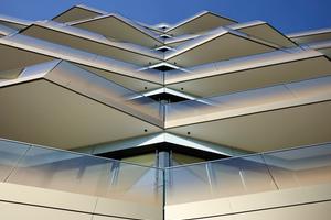 """<div class=""""bildtext"""">Die trapezförmigen Balkone, die das komplette Gebäude mit ihrer regelhaft unregelmäßigen kristallinen Struktur umhüllen, prägen die Ansicht.</div>"""