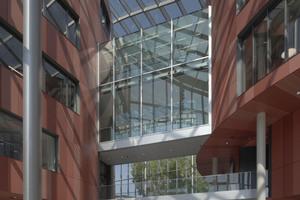 """<div class=""""bildtext"""">Die Gebäudeteile im diagonallaufenden Atrium werden in den oberen Stockwerken durch Glasbrücken verbunden.</div>"""