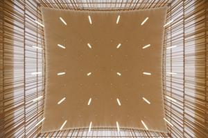 Innenansicht: Die Metalldachkonstruktion sorgt mit der filigranen Holzlamellen-Verkleidung für eine besondere Lichtstimmung.<br />