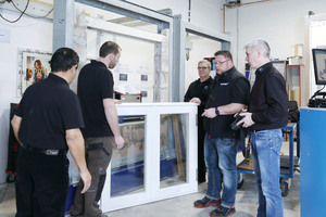 """<div class=""""bildtext"""">Prüfstellenleiter Alexander Dupp (2.v.r.) erklärt den Kunden den Aufbau des Tests für das mitgebrachte Fensterelement.</div>"""