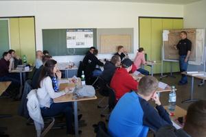 "<div class=""bildtext"">Aufmerksame Schüler während des Expertenvortrags von Benjamin Maus.</div>"