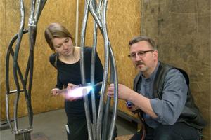 "<div class=""bildtext"">Jasmin Sauer an einem Lufthammer beim bearbeiten einer geschmiedeten Stahlstütze.</div>"