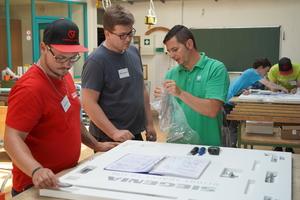 """<div class=""""bildtext"""">Der Technische Lehrer Antonio Bava (r.) gab den Auszubildenden bei der Montage des Alufensters Hilfestellung.</div>"""