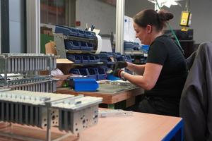 An den Montagearbeitsplätzen werden Kleinteile zu einem Großteil händisch in das Türschloss eingebaut.<br />