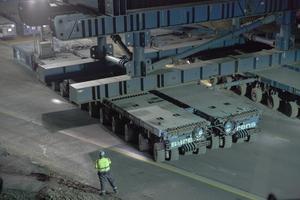 """<div class=""""bildtext"""">Das Einfahren der Brücke mit SPMTs. Die Arbeiter mit den Warnwesten steuern mit Funkfernsteuerungen einmal die vordere und einmal die hintere Einheit von je 8 zusammengeschalteten Fahrzeugen.</div>"""
