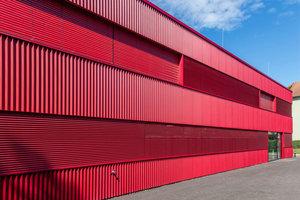 Die Fassade, bestehend aus roten Metalllamellen, fasst alle Baukörper zu einem Ensemble zusammen.