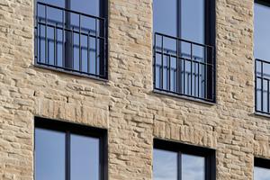 """<div class=""""bildtext"""">In die Fassade eingebettet sind bodentiefe Fenster aus 6 cm schmalen Stahlverbundprofilen. Stahlgitter leisten die Absturzsicherung.</div>"""