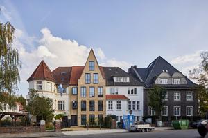 """<div class=""""bildtext"""">Die Gesamtansicht der Häusergruppe in der Dechaneistraße in Münster; mittig ist der 2020 fertiggestellte Neubau von Mensen + Zora Architekten zu sehen.</div>"""