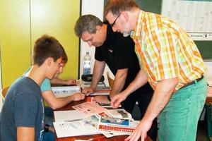 """<div class=""""bildtext"""">Experte Roberto Weyda (m.) und Lehrer Michael Höhler (r.) unterstützen dessen Schüler beim Bearbeiten des Lernjobs</div>"""