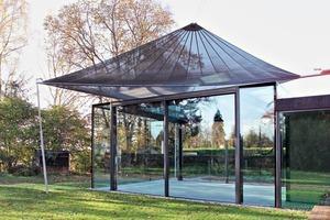 """<div class=""""bildtext"""">Die Bäume und das Segel schützen im Pavillon vor Sonnenstrahlen.</div>"""