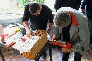 """<div class=""""bildtext"""">Schüler Hermann Voth (l.) mit dem Experten Roberto Weyda beim Setzen eines Injektionsankers in einen Hochlochziegel.</div>"""
